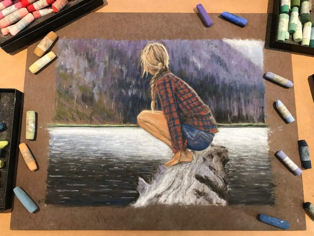 The completed piece of artwork, still on its board, surrounded by a variety of pastels.