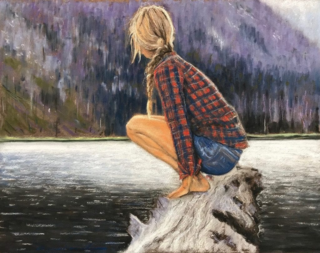 A blonde haired women in a lumberjack shirt, balanced on a large piece of driftwood, looking out in the steep sided lake.