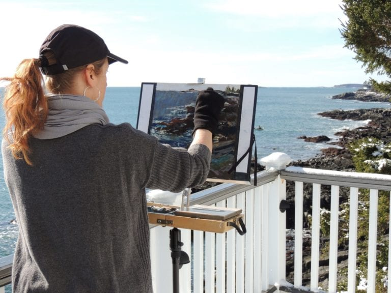 Lyn at her easel, on a rugged coastline.