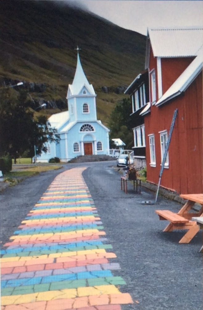 A photo of a small white church, with multicoloured paved path, leading post some houses.
