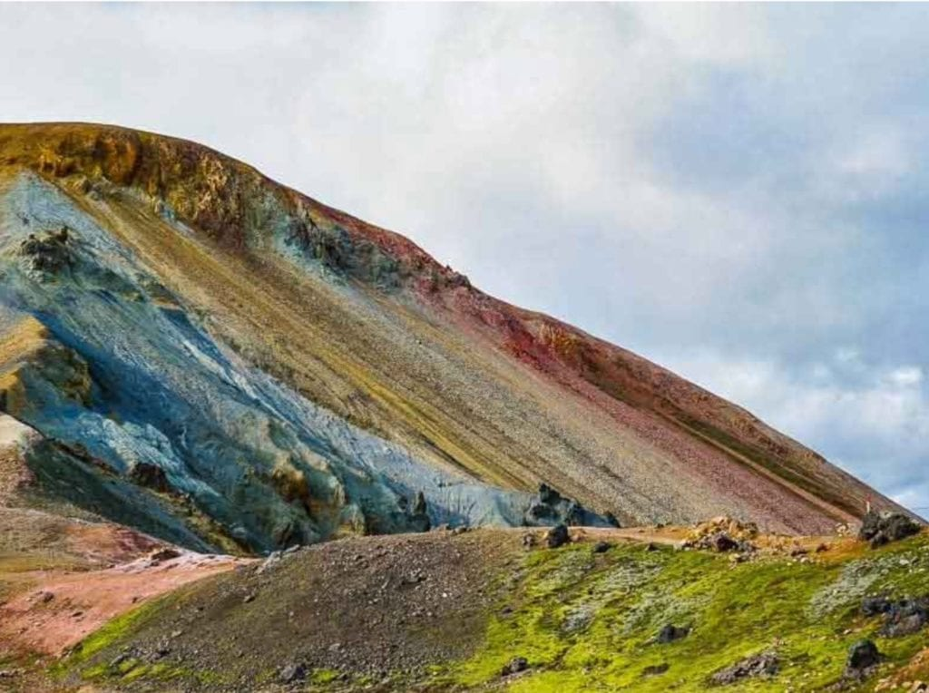 A landscape photo from Iceland, showing a variety of coloured layers in a hillside.