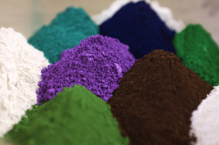 Multiple heaps of different coloured pigments.