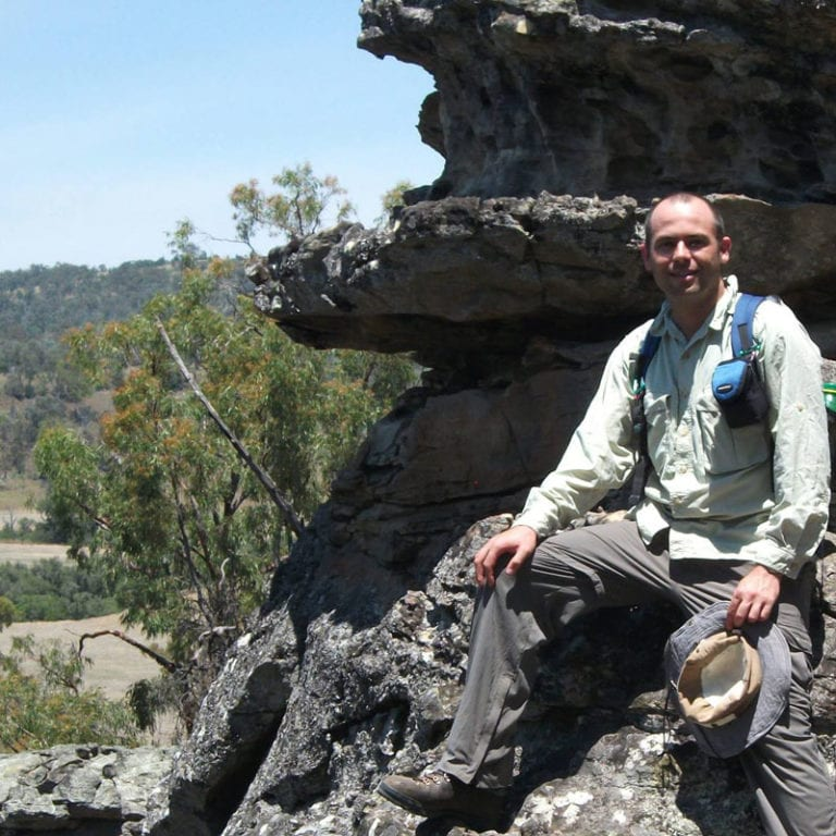 A photo of Brent sitting on a rock, in the Australian outdoors.