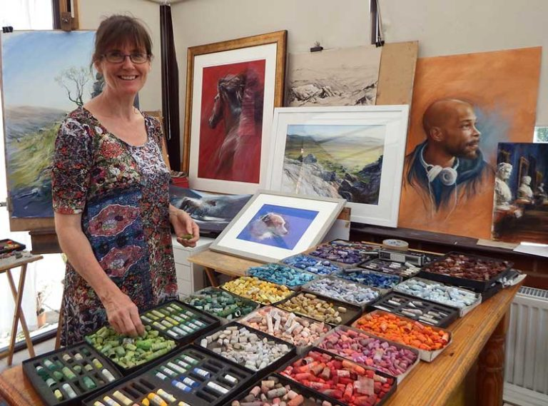 Rebecca in her studio with a huge selection of Unison Colour pastels laid out on a table.