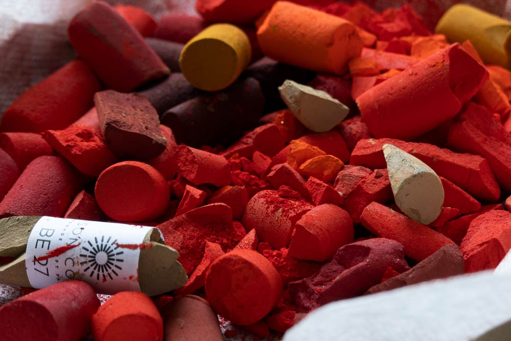 Tray of broken red Unison Colour pastels.