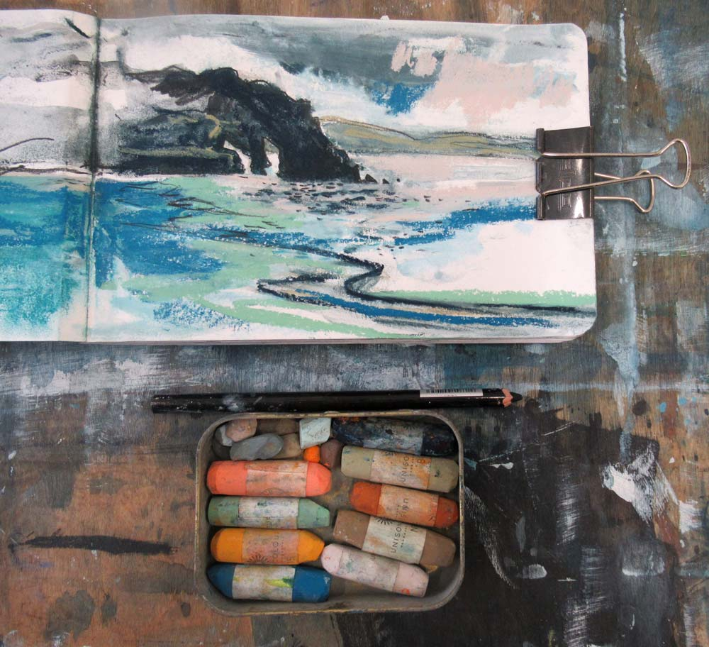 Sketchbook with small tin of pastels.