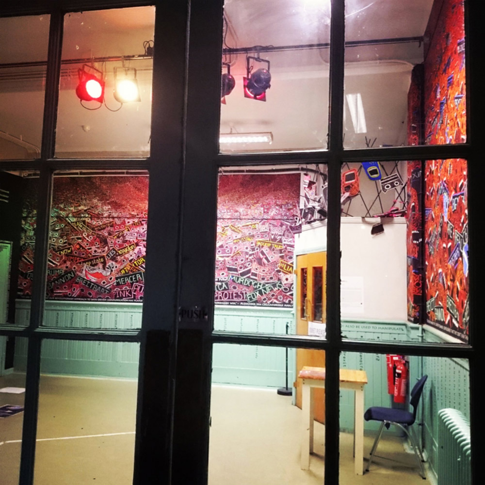 Looking in through a paned window, into the exhibition.