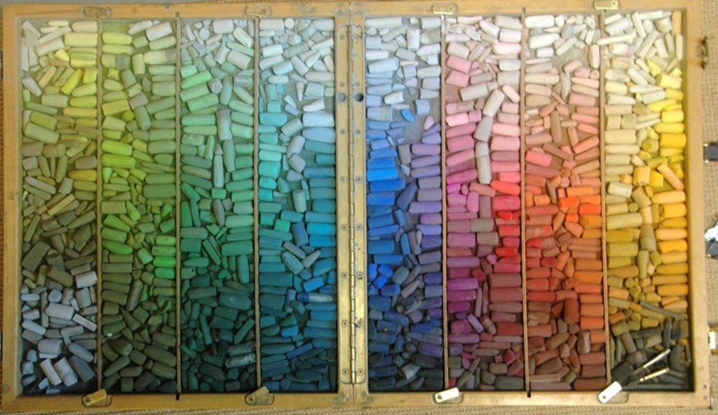 Huge collection of soft pastels, neatly arranged by colour.